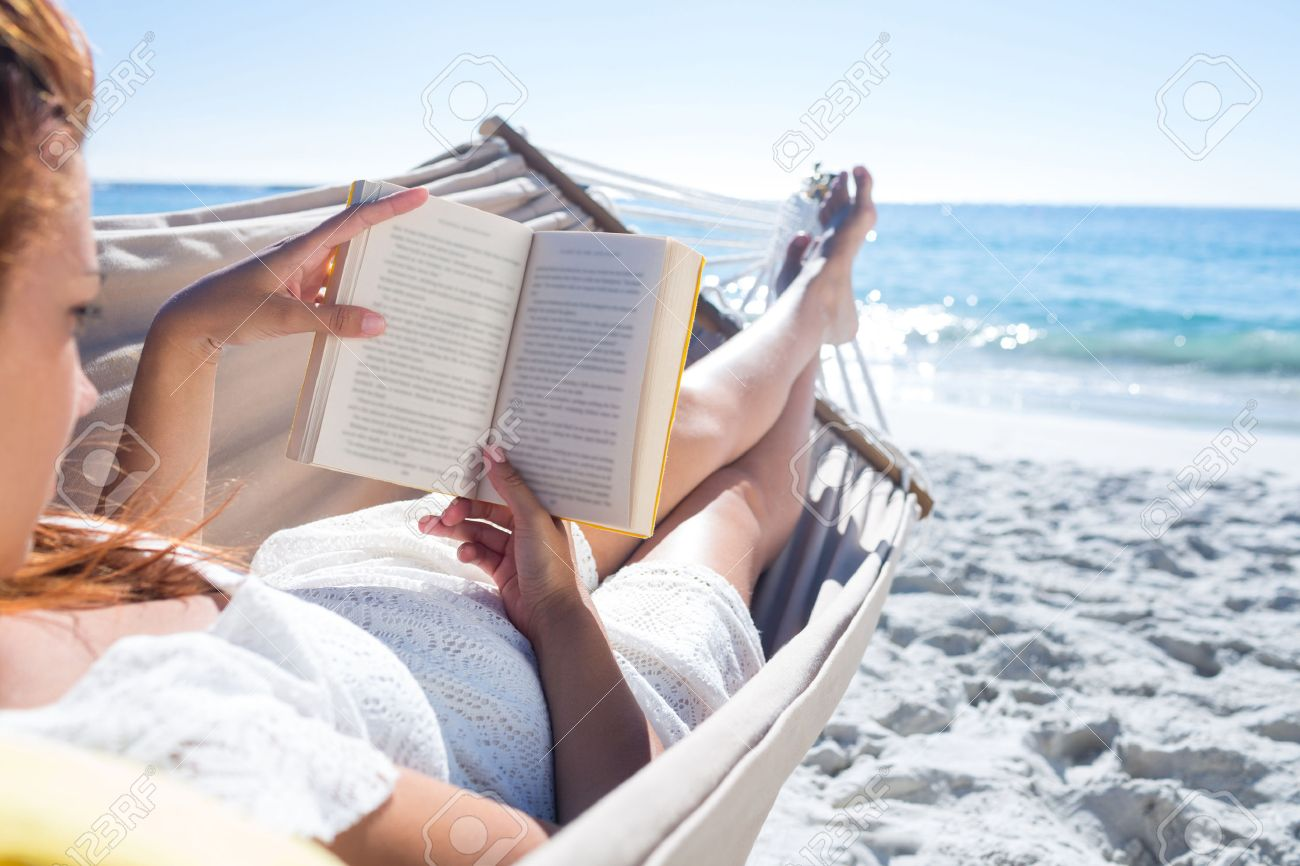 brunette reading a book while relaxing in the hammock at the stock