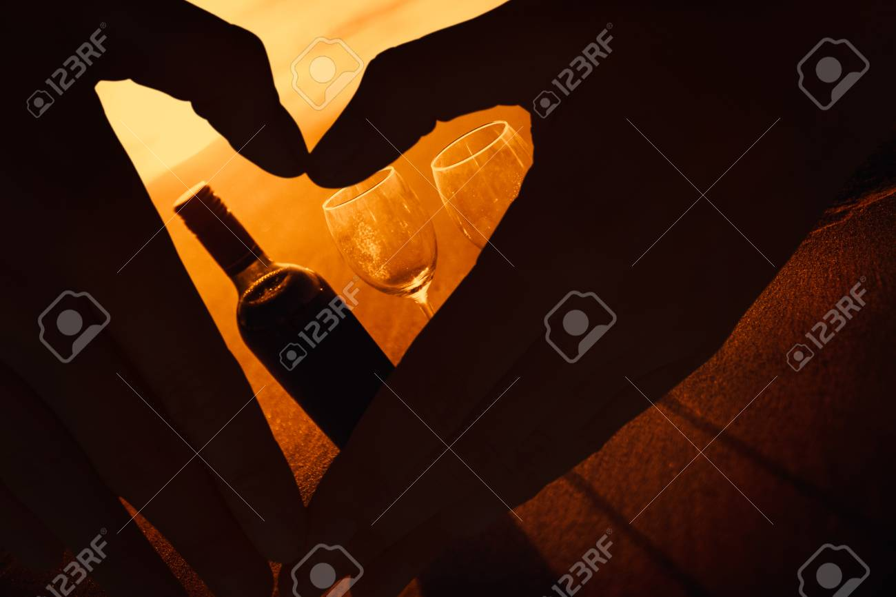 Woman making heart shape with hands against bottle of vine with