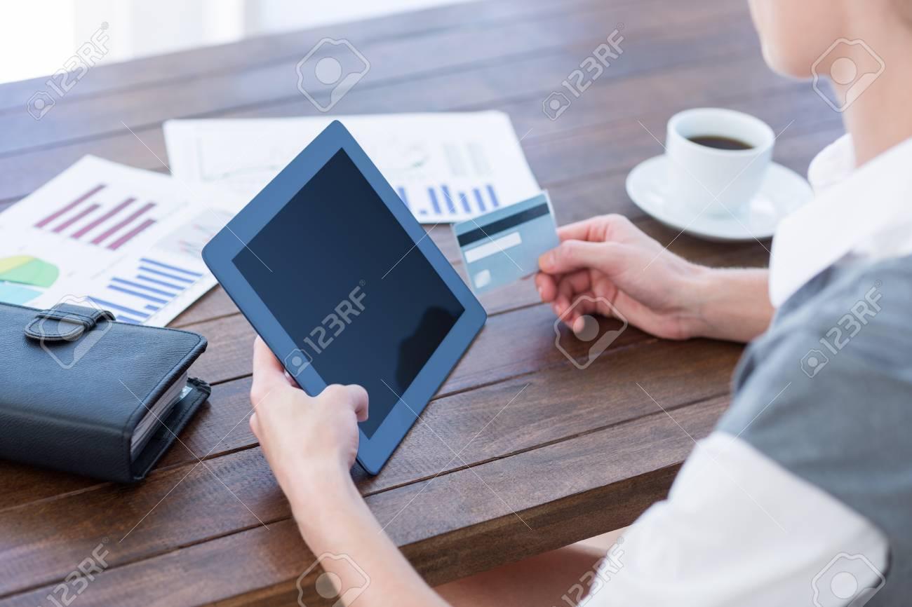 Businesswoman using tablet pc et la tenue de la carte de crédit dans