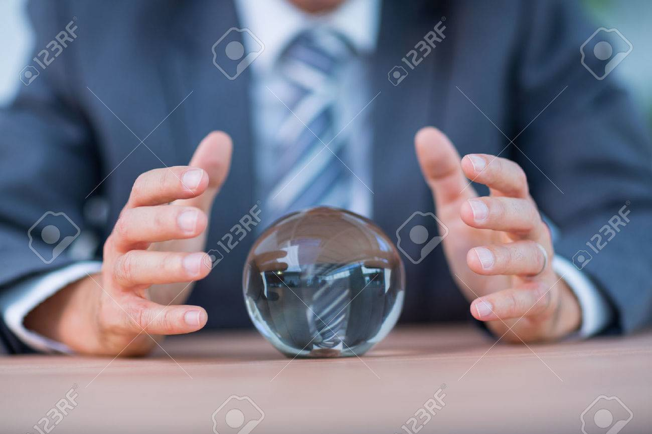 Businessman forecasting a crystal ball in the office - 42324684
