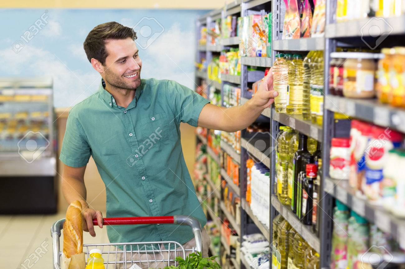 Smiling Man Taking A Oil In The Aisle At Supermarket Stock Photo ...