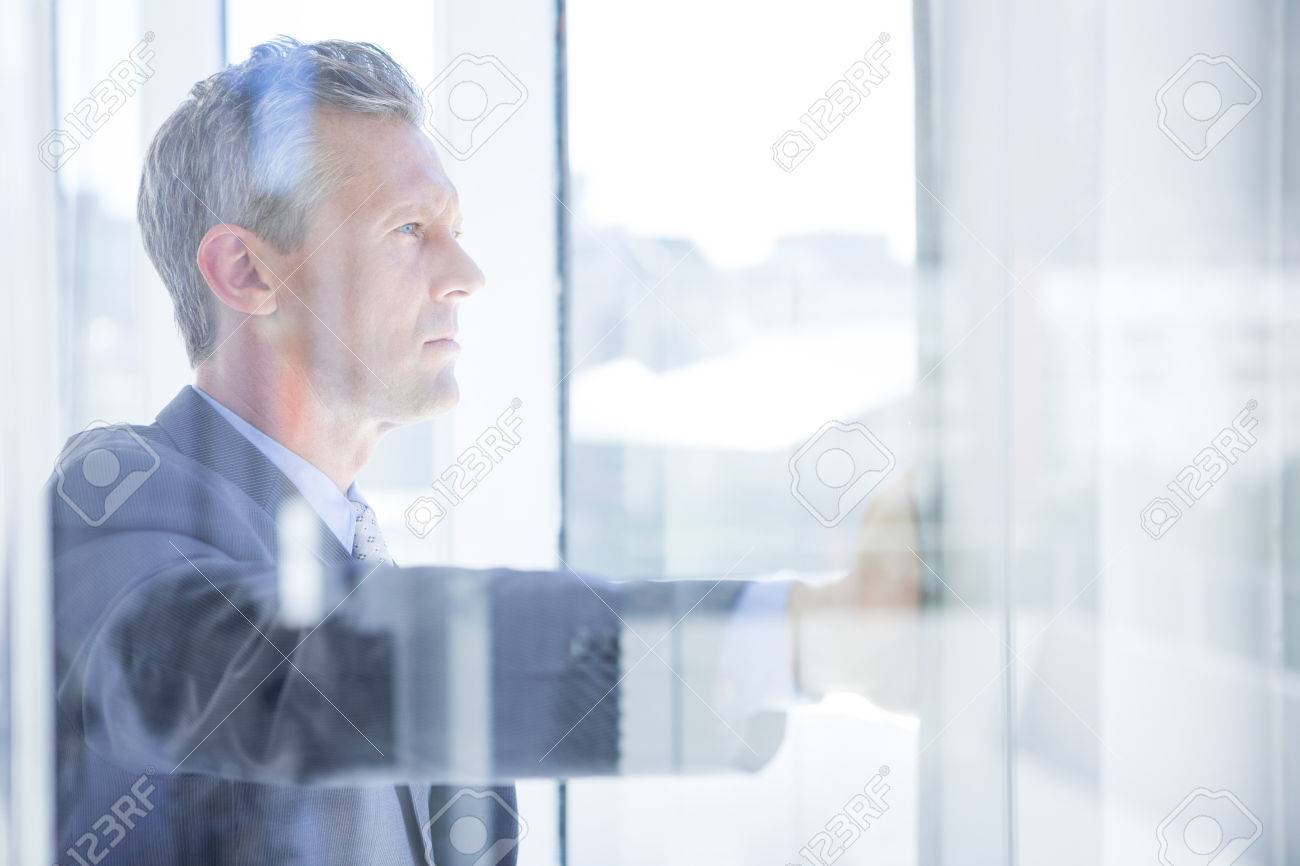 Thinking businessman in the office looking through the window - 46066928