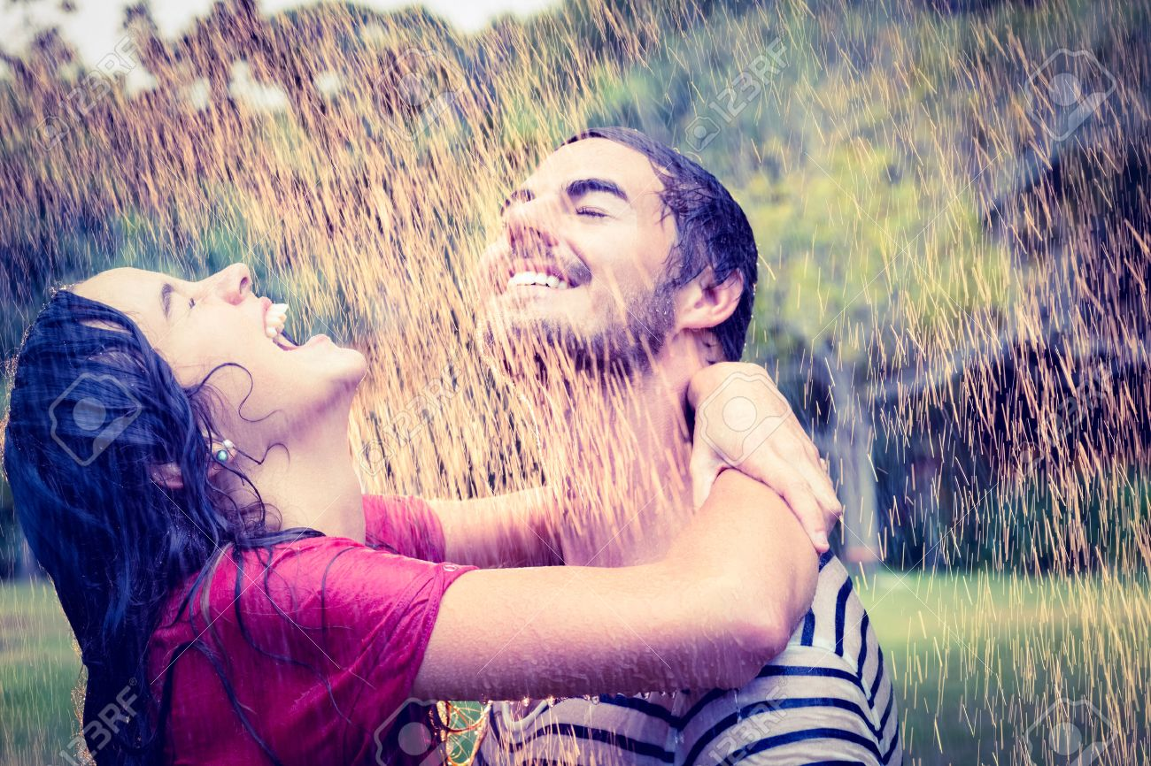 Cute couple hugging under the rain in the park