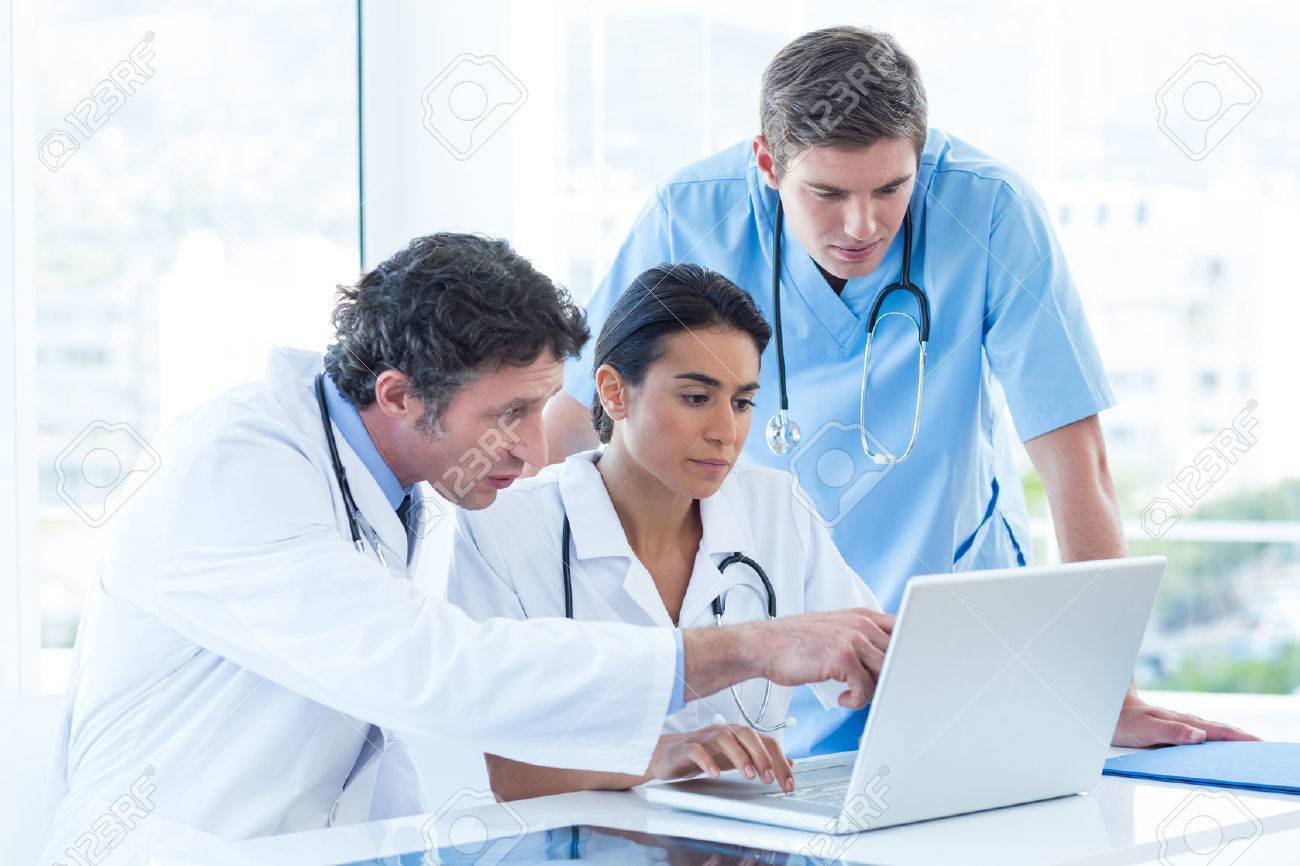 Team of doctors working on laptop in medical office Stock Photo - 42577998