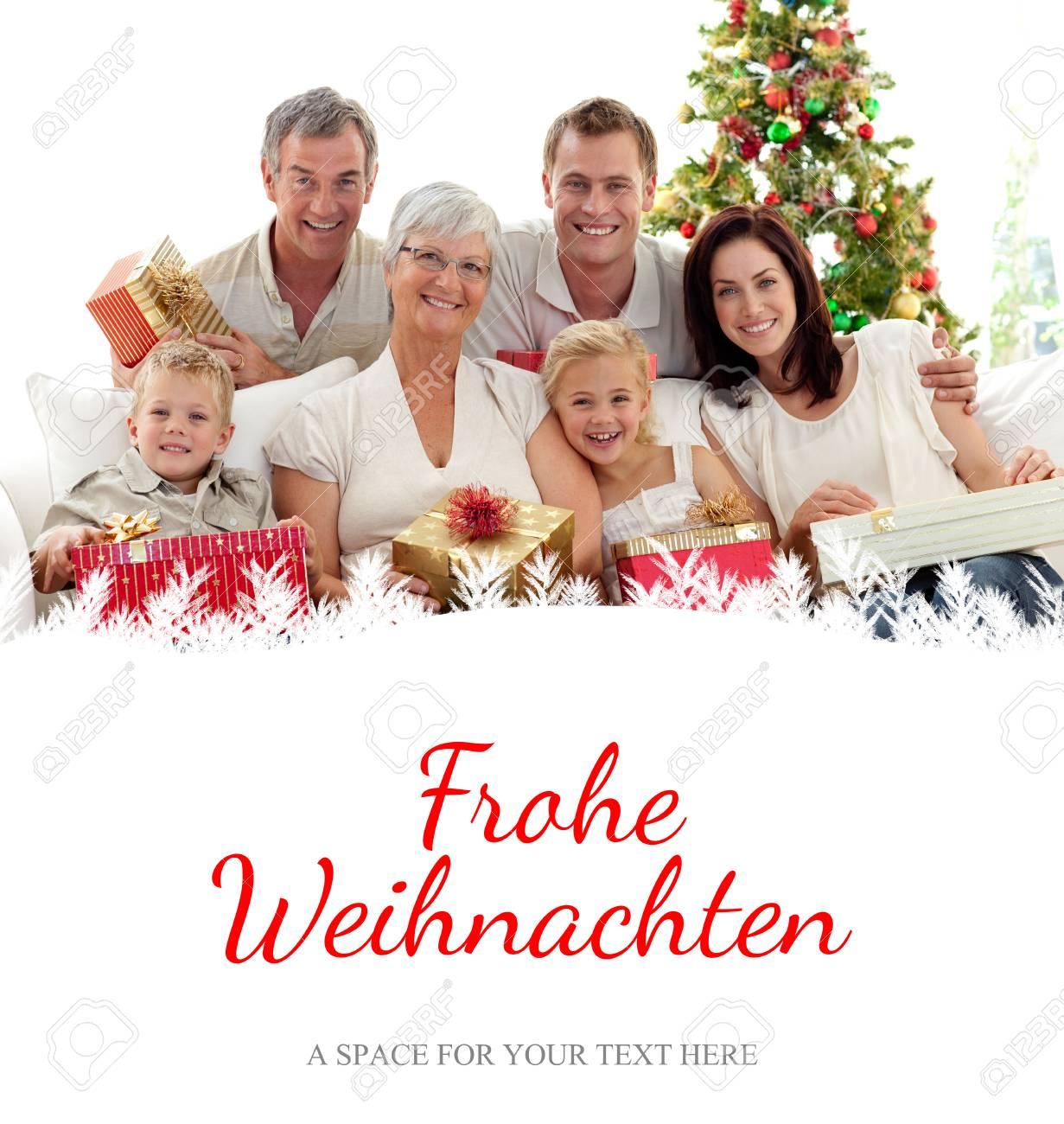 Familie Hält Weihnachtsgeschenke Zu Hause Gegen Weihnachtsgruß Auf ...