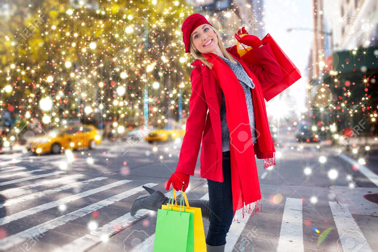 happy blonde in winter clothes holding shopping bags against..