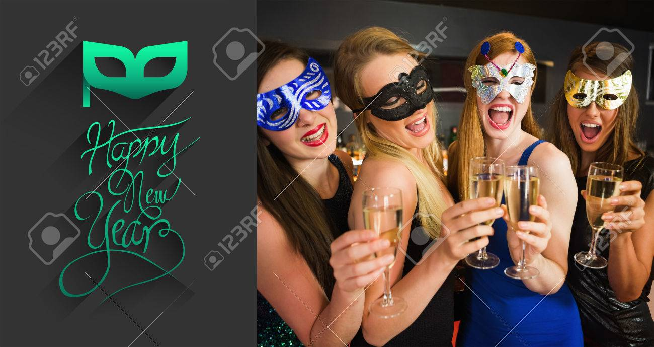 attractive friends with masks on holding champagne glasses against classy new year greeting stock photo