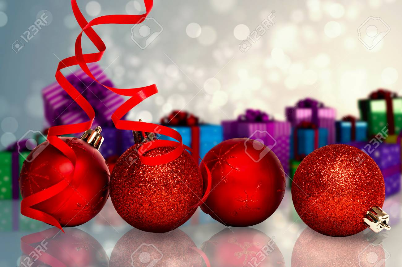 four red christmas ball decorations against light design shimmering on silver stock photo 42972156