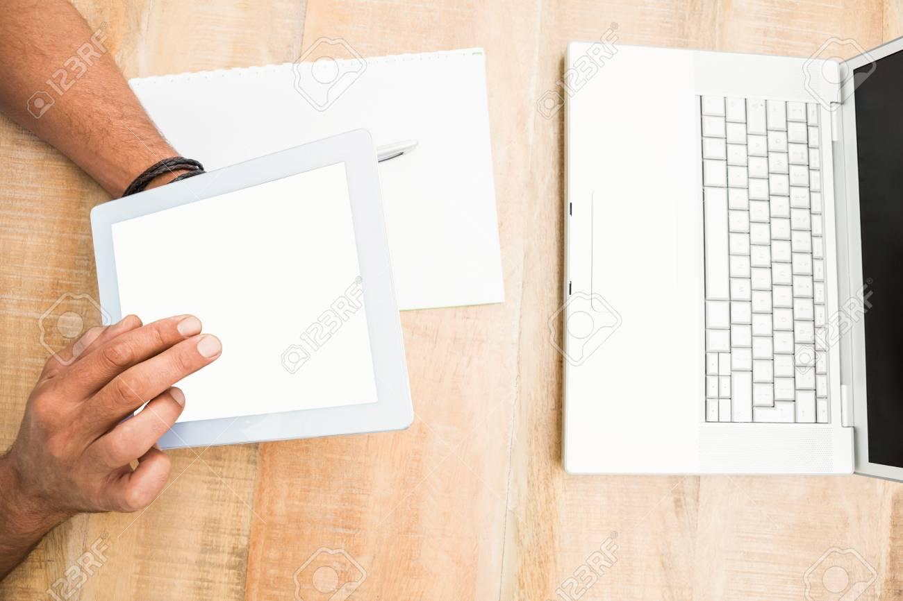 Mains en utilisant une tablette écran blanc sur le bureau en bois