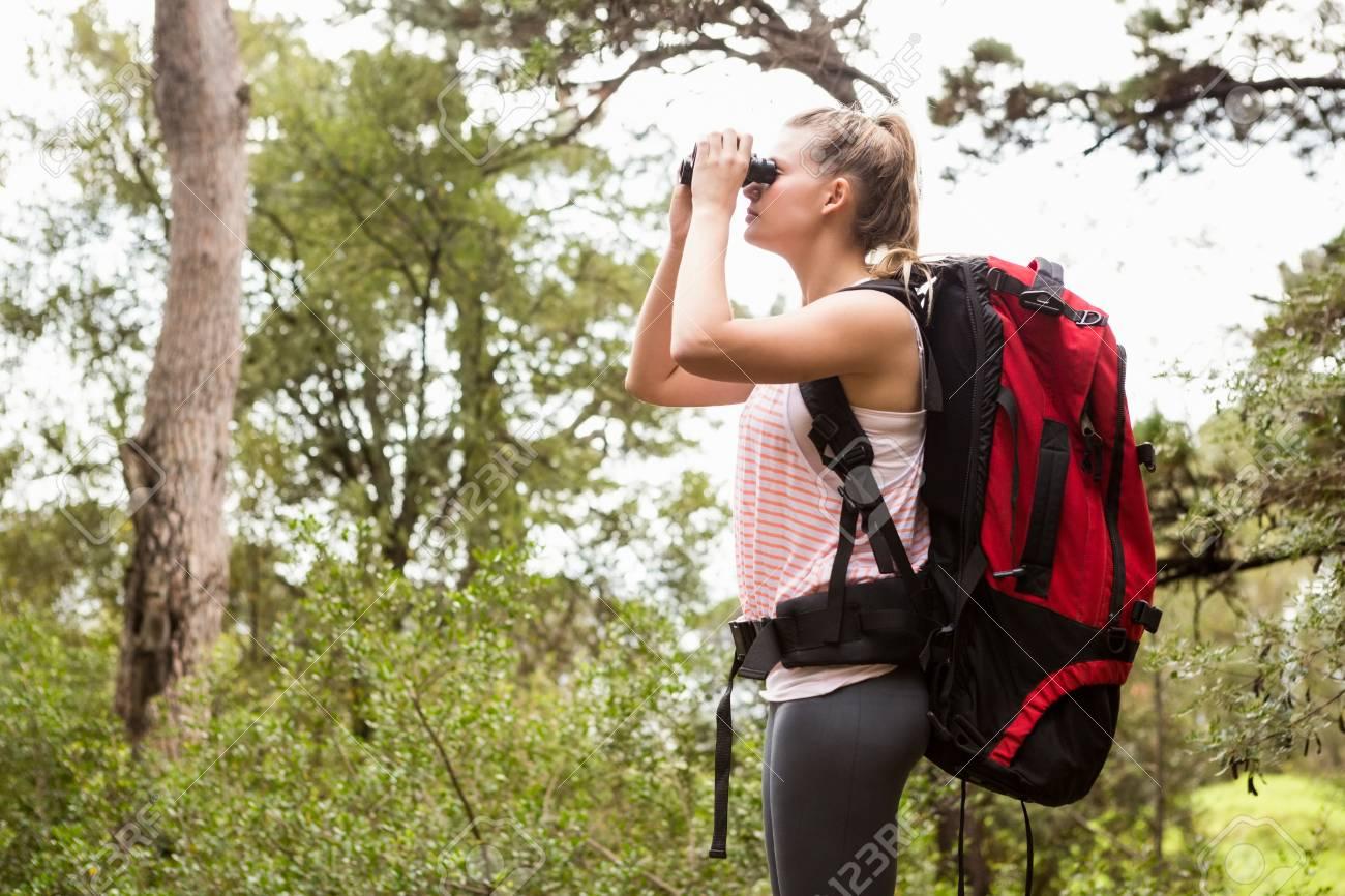 Blonder wanderer der durch ferngläser in der natur schaut