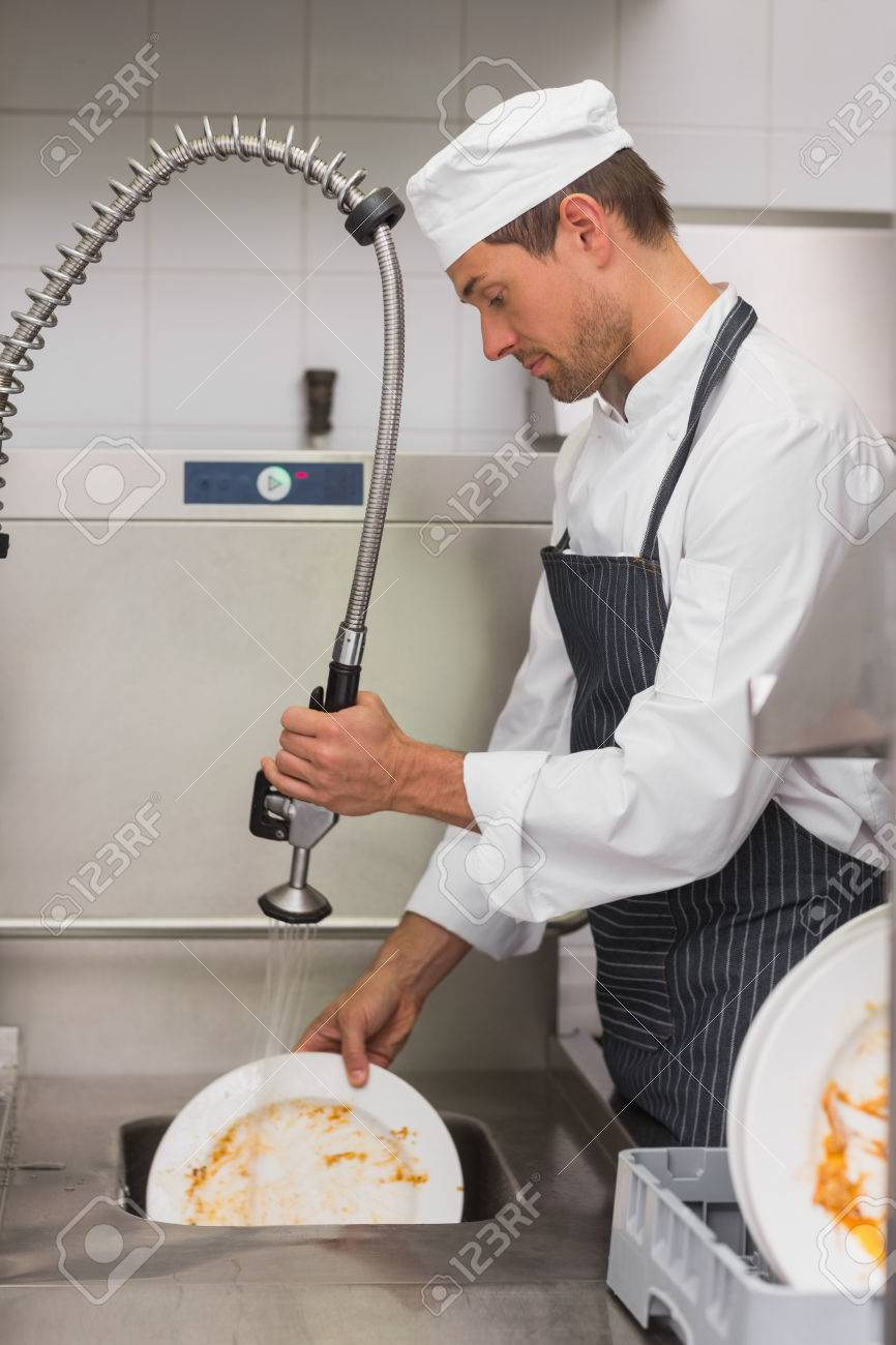 Kitchen Porter Cleaning Plates In Sink In Professional Kitchen Stock Photo    49301398