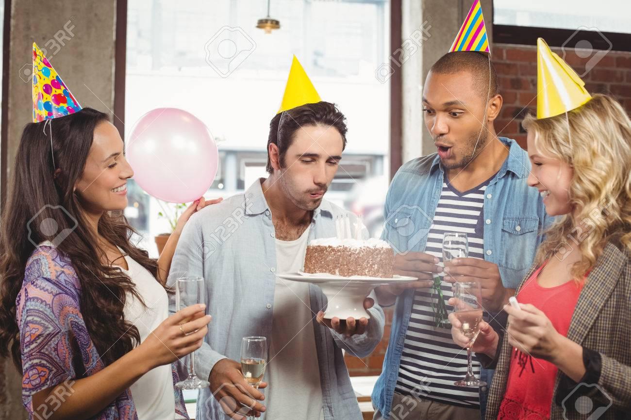 Man Blast Kerze Auf Kuchen Wahrend Kollegen Im Buro Lachelnd