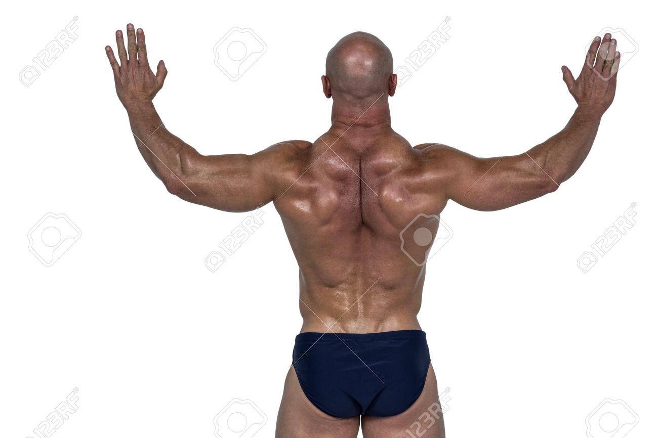 Banque d images - Vue arrière de l homme musclé avec les bras levés sur le  fond blanc 6764025c95b