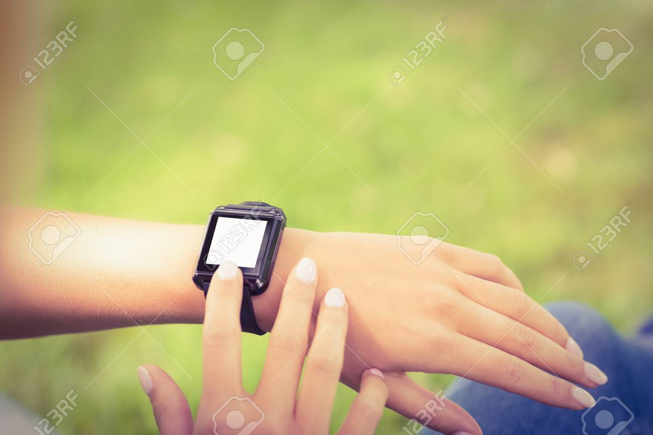 High angle view of woman touching smart watch while sitting in