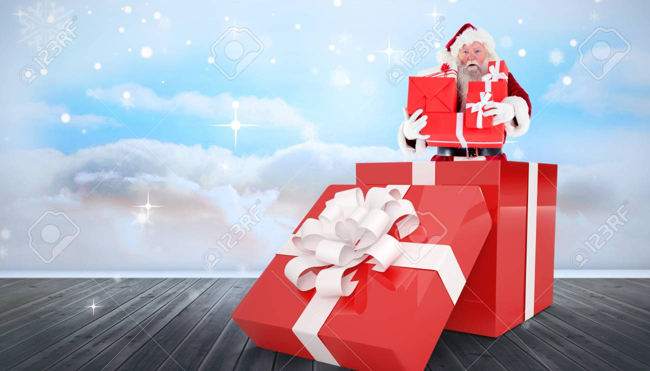 santa standing in large gift against clouds in a room stock photo