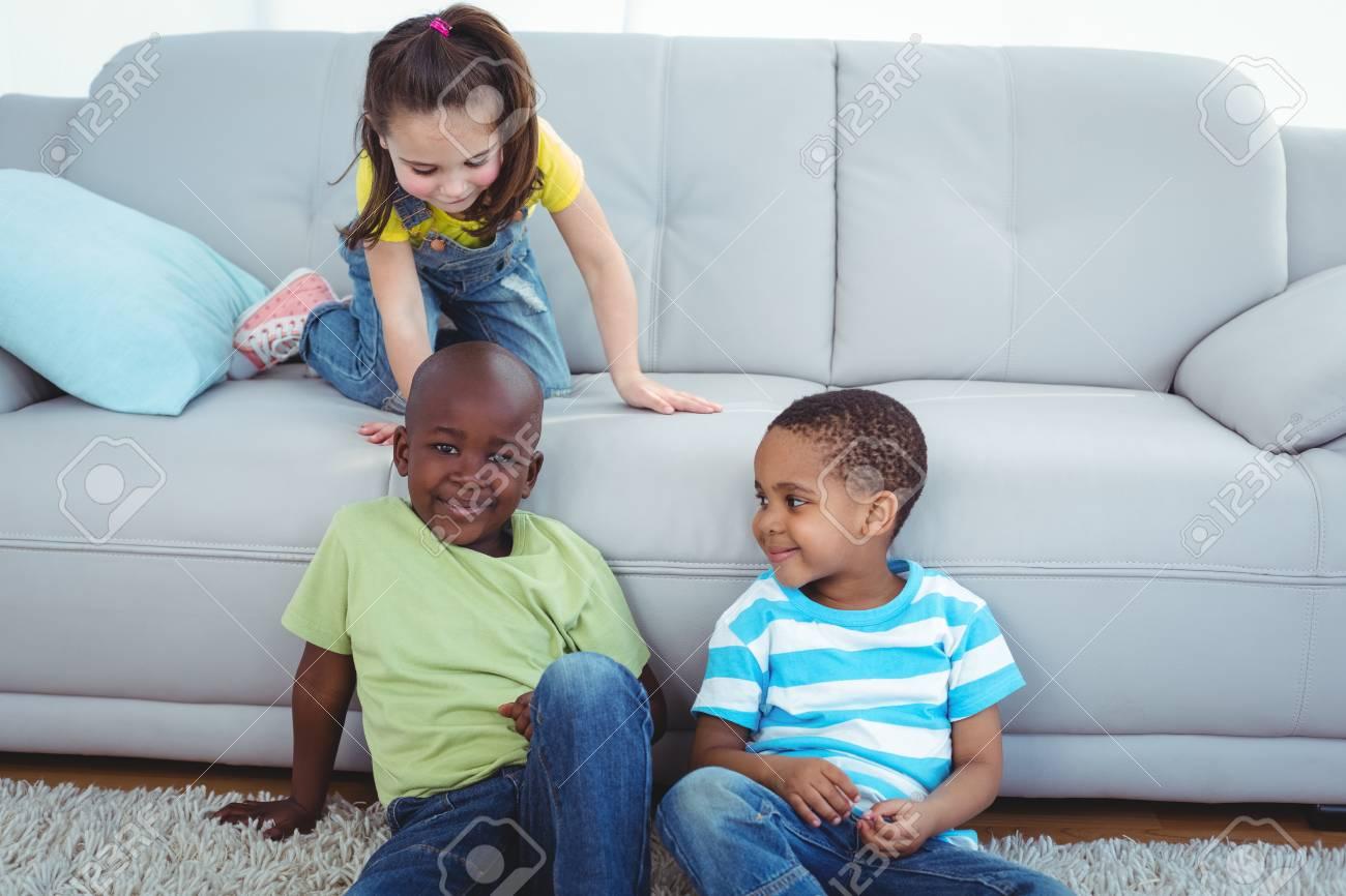 Lachelnde Kinder Die Durch Die Couch Auf Dem Boden Sitzen