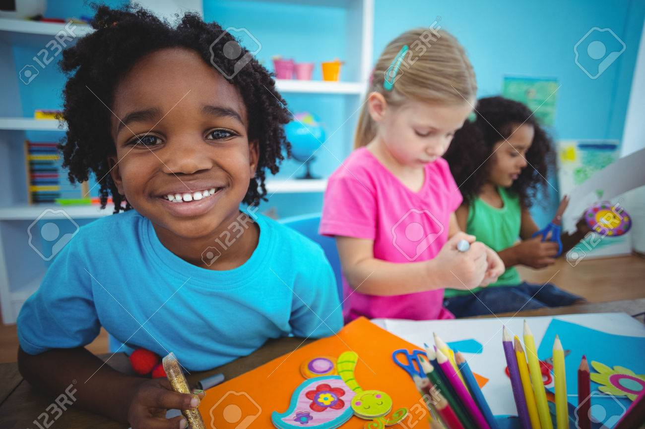 Happy kids using modelling clay together at their desk Stock Photo - 47508405