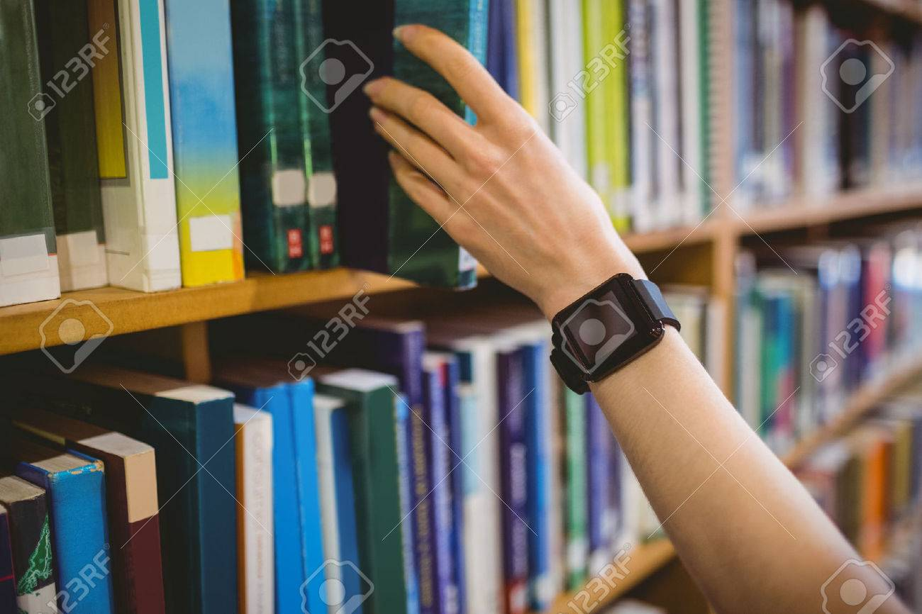 Student picking book in library wearing smart watch at the university Stock Photo - 47507059
