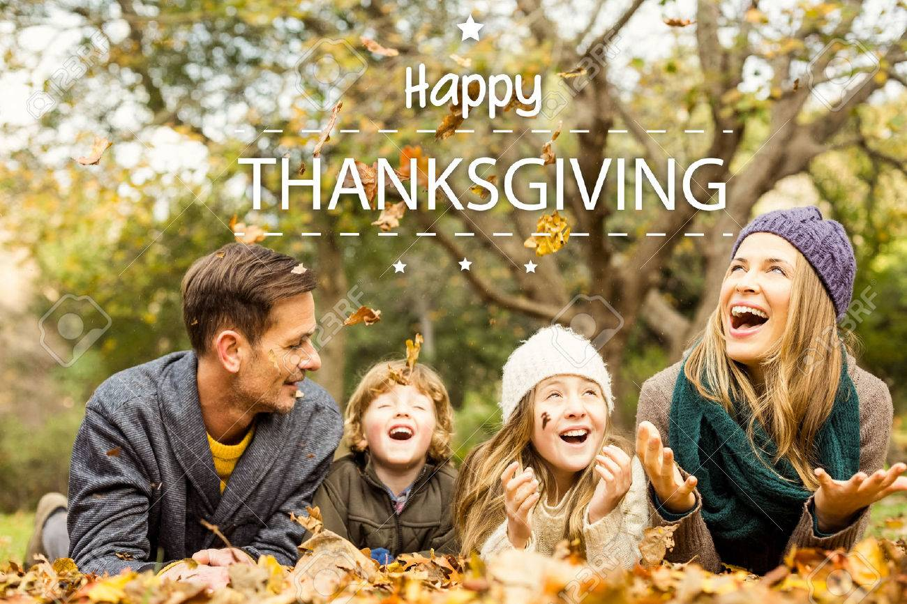 Happy thanksgiving against smiling young family throwing leaves around Stock Photo - 47543296