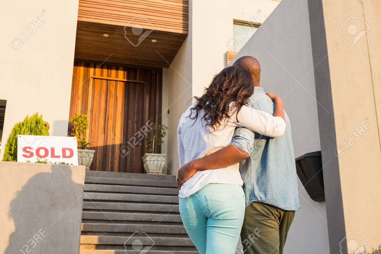 Back view of couple with arms above after buying house Stock Photo - 48190402