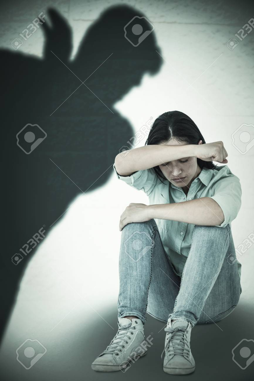 Sad woman sitting on the floor and hiding her face against silhouette of man with raised hand - 48540480