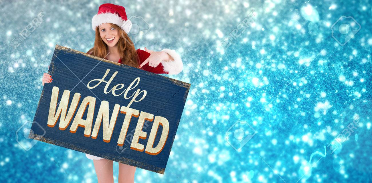 Christmas Help Wanted.Festive Redhead Smiling At Camera Holding Poster Against Vintage