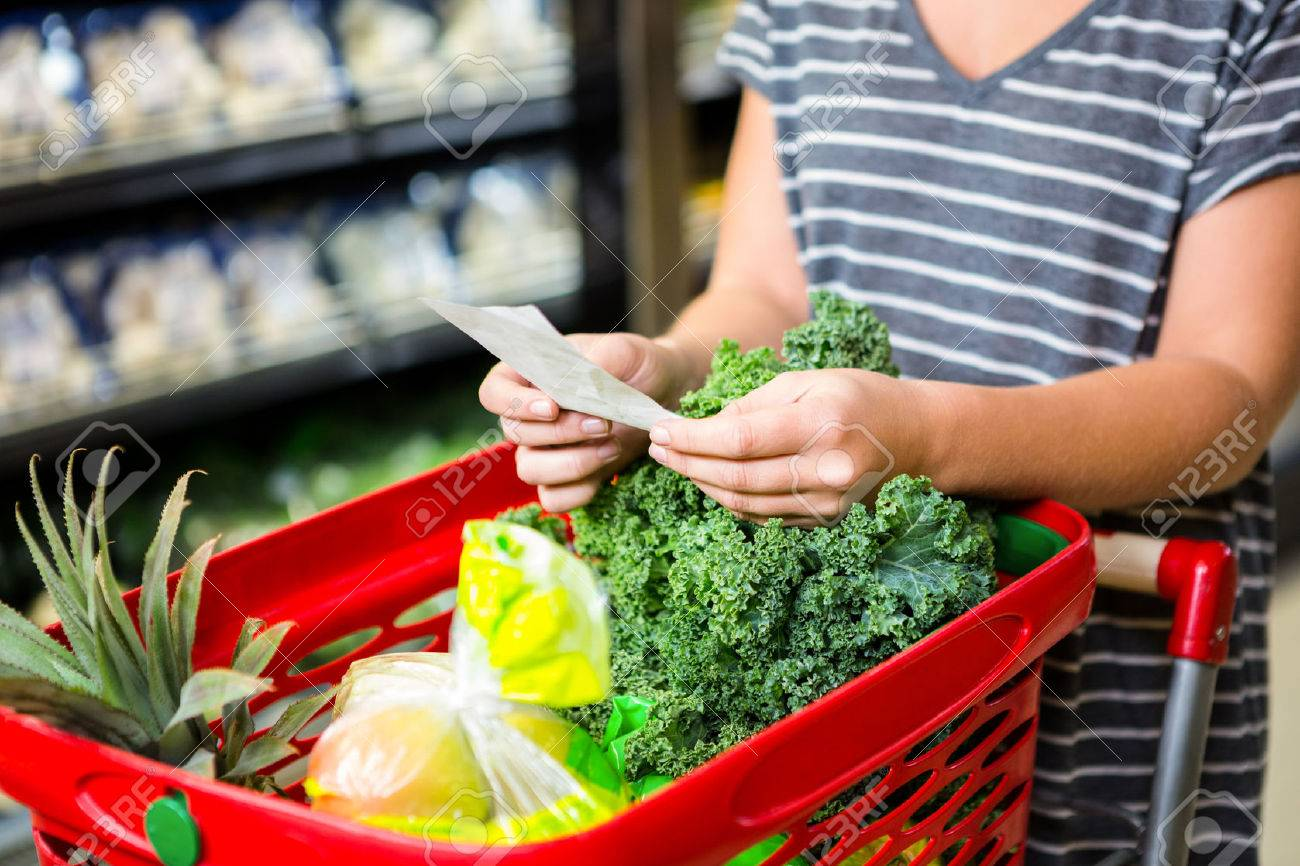 Woman with red basket holding list in supermarket Stock Photo - 50632177
