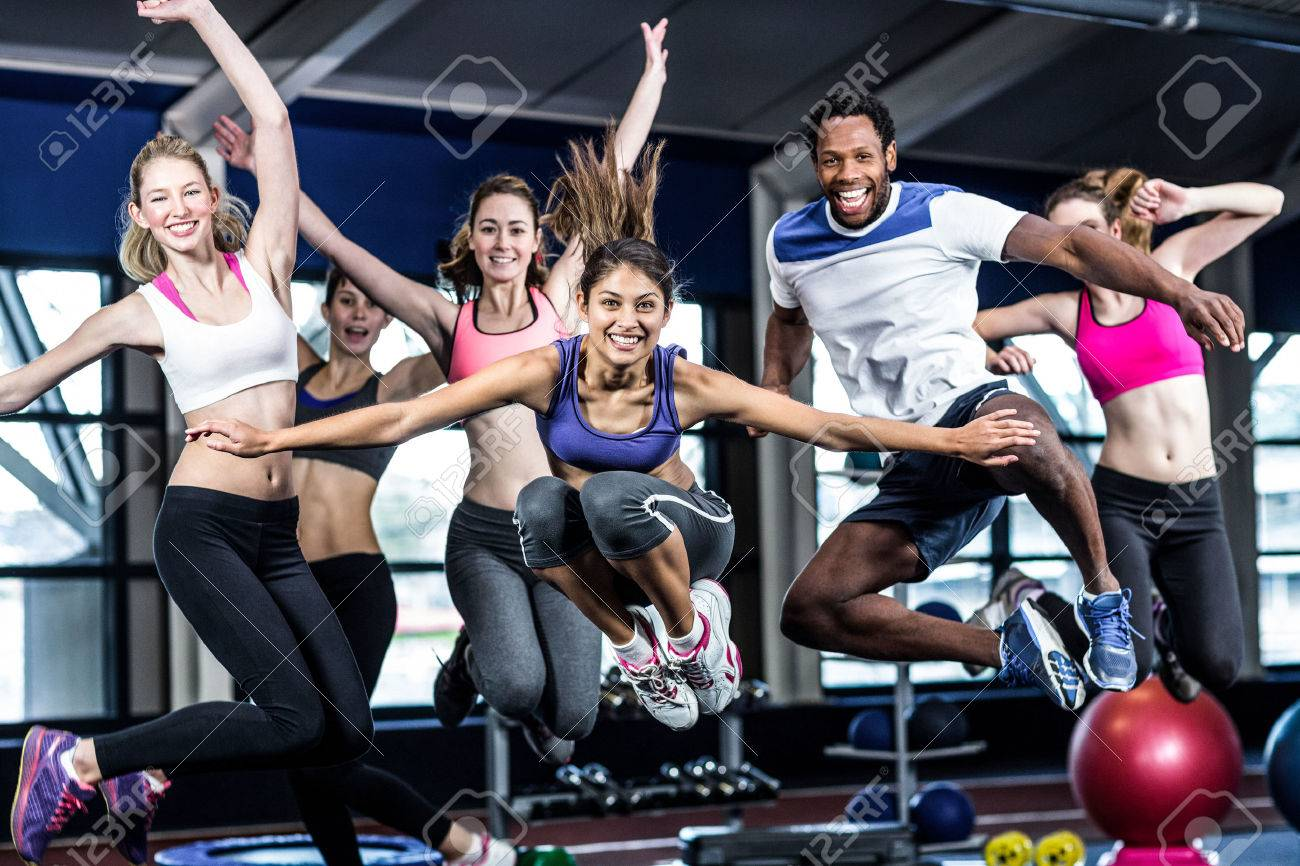 Fit group smiling and jumping in gym - 50632898