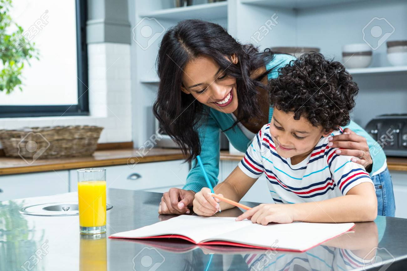 Kind Mother Helping Her Son Doing Homework In Kitchen Stock Photo ...
