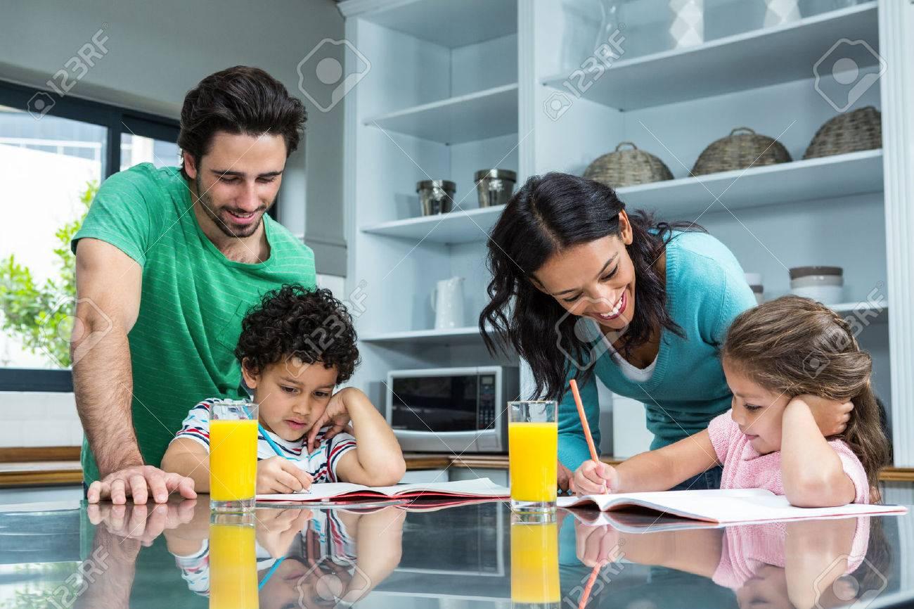 Parents Helping Their Children Doing Homework In The Kitchen Stock ...