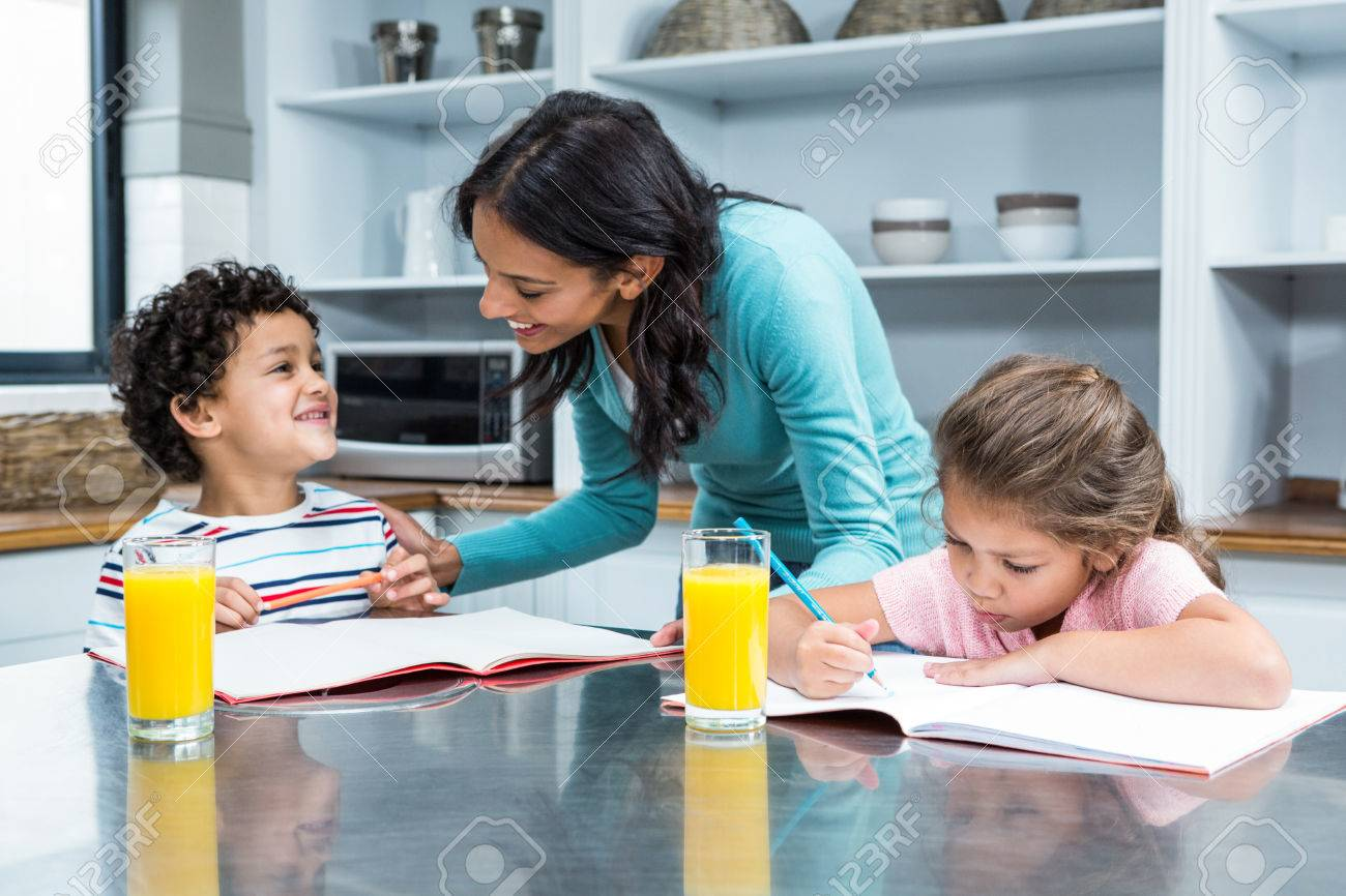 Kind Mother Helping Her Children Doing Homework In Kitchen Stock ...