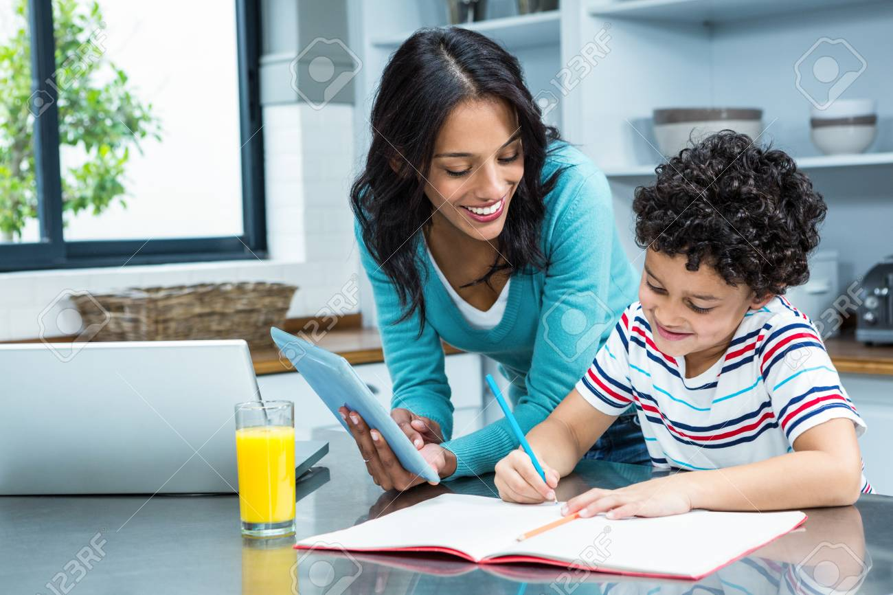 Kind Mother Helping Her Son Doing Homework In Kitchen While Using ...