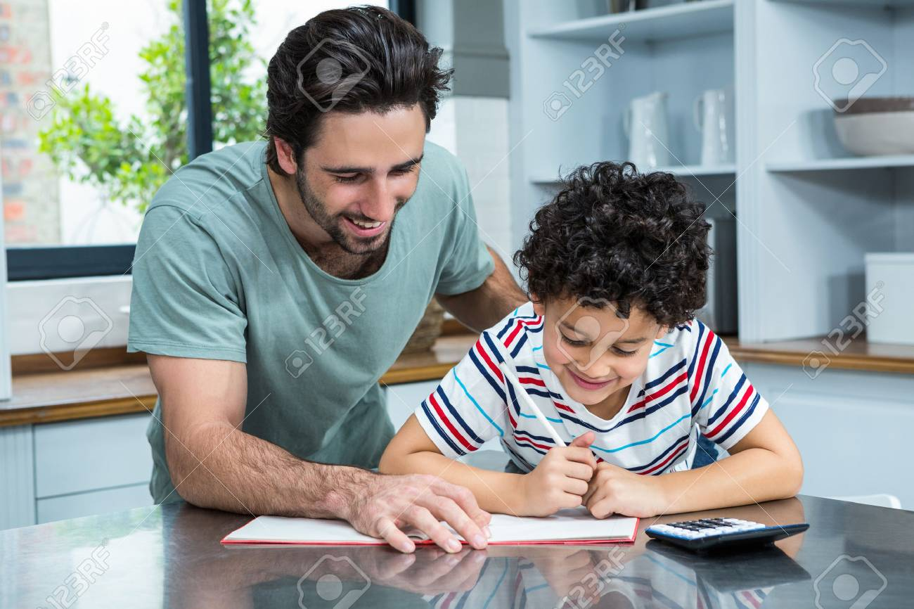 Kind Father Helping His Son Doing Homework In The Kitchen Stock ...