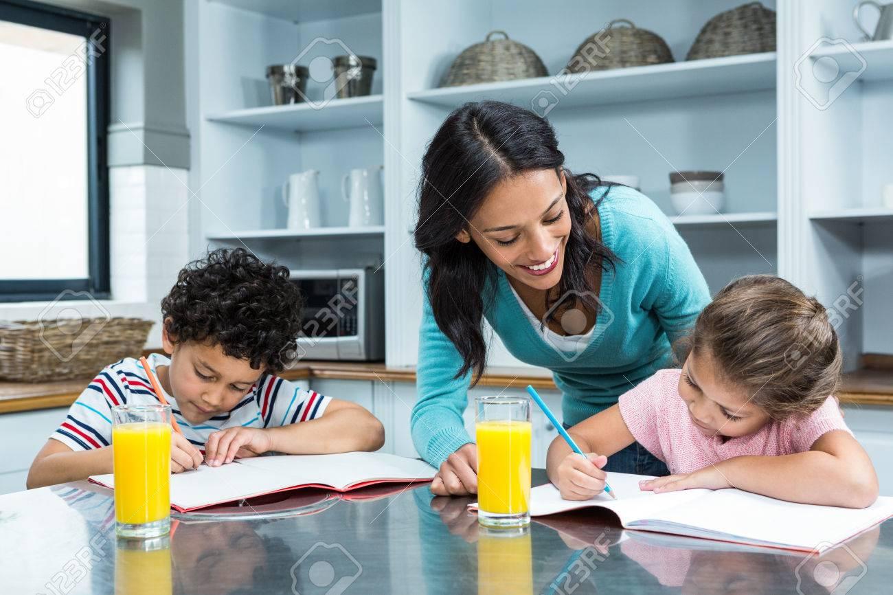 Kind Mother Helping Her Children Doing Homework In Kitchen Stock ...