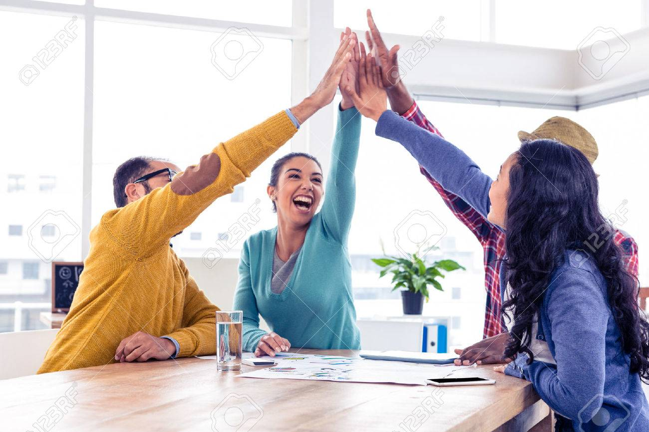 Cheerful business team doing high five while sitting in creative office Stock Photo - 51360061