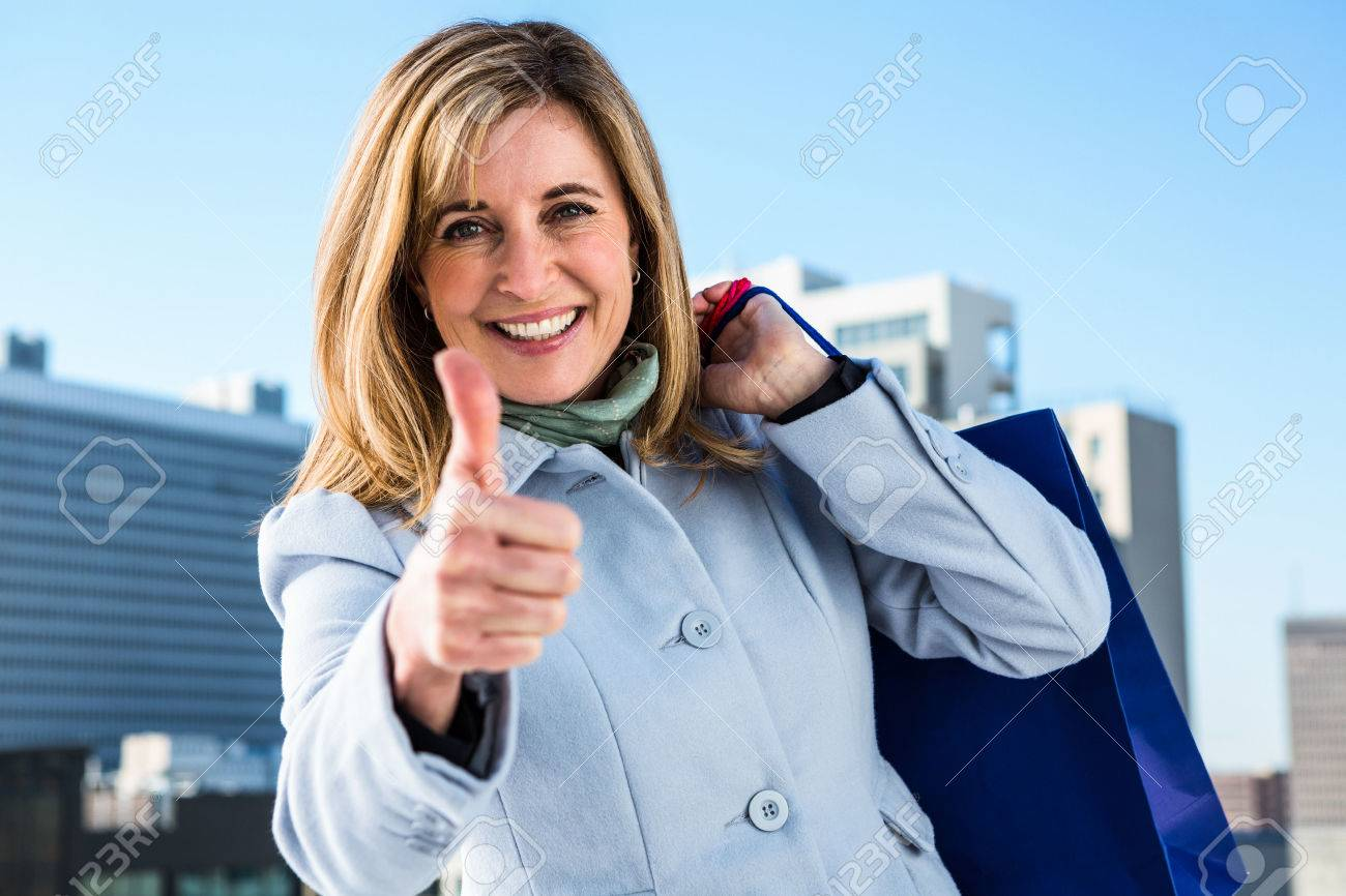 Woman doing a thumbs up during her shopping in town Stock Photo - 51330935