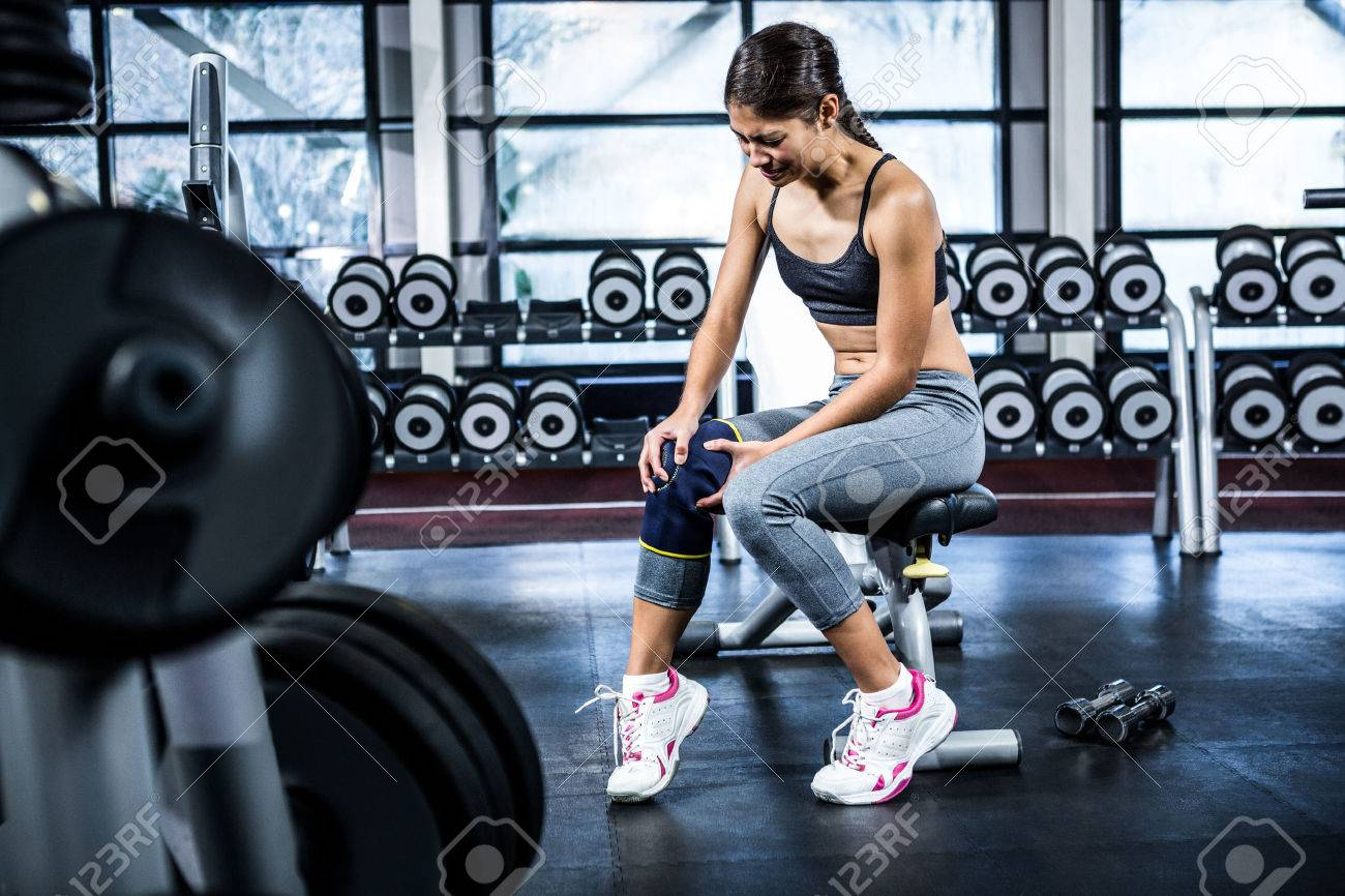 Fit woman having knees pain at gym Stock Photo - 51521597