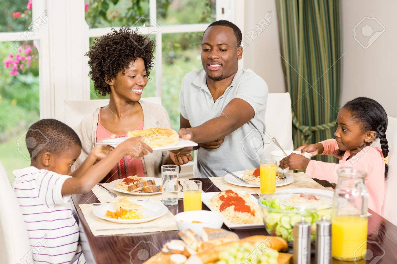 Happy family eating together at home Stock Photo - 51417944