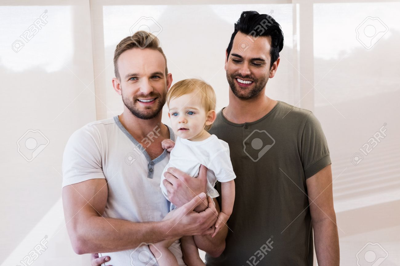 Smiling gay couple with child at home Stock Photo - 52102476