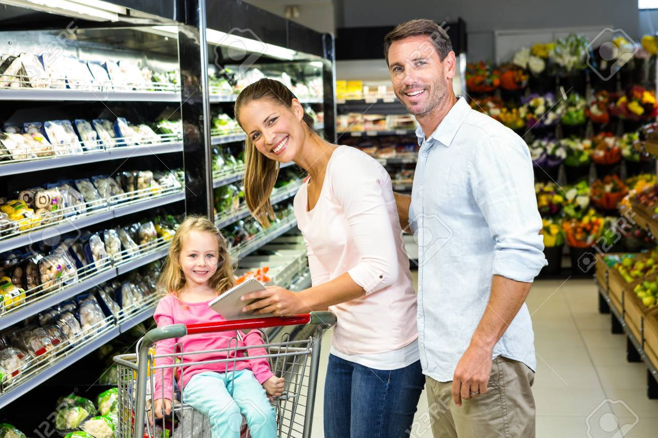 happy family checking grocery list in grocery store stock photo