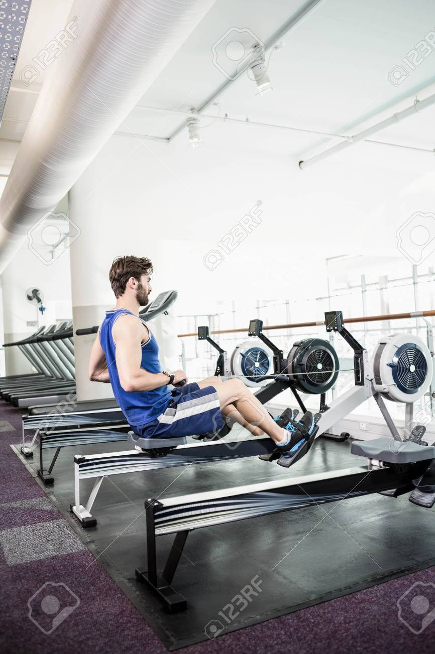 Handsome man doing exercise on drawing machine at the gym stock