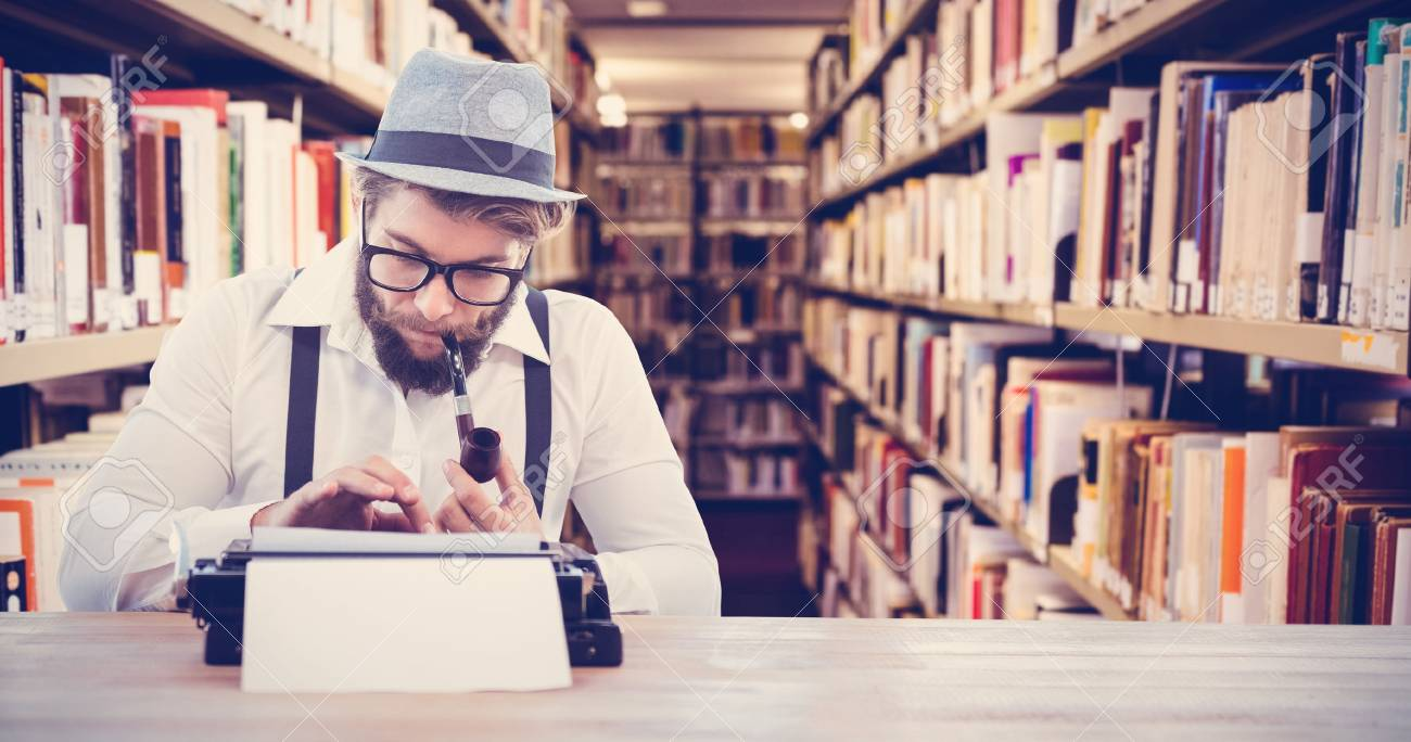 Hipster Smoking Pipe While Working At Desk Against Close Up Of A Bookshelf Stock Photo