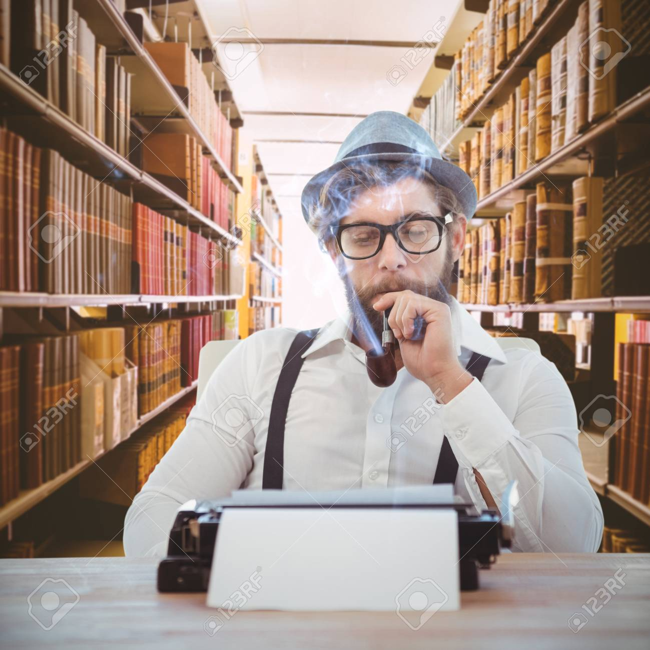 Hipster Smoking Pipe While Sitting Looking At Typewriter Against Close Up Of A Bookshelf Stock Photo