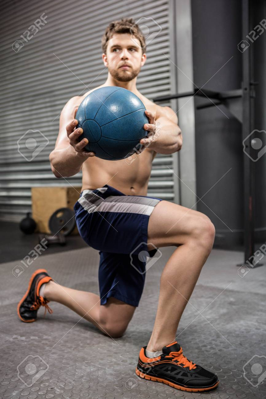 shirtless man training with medicine ball at the crossfit gym stock