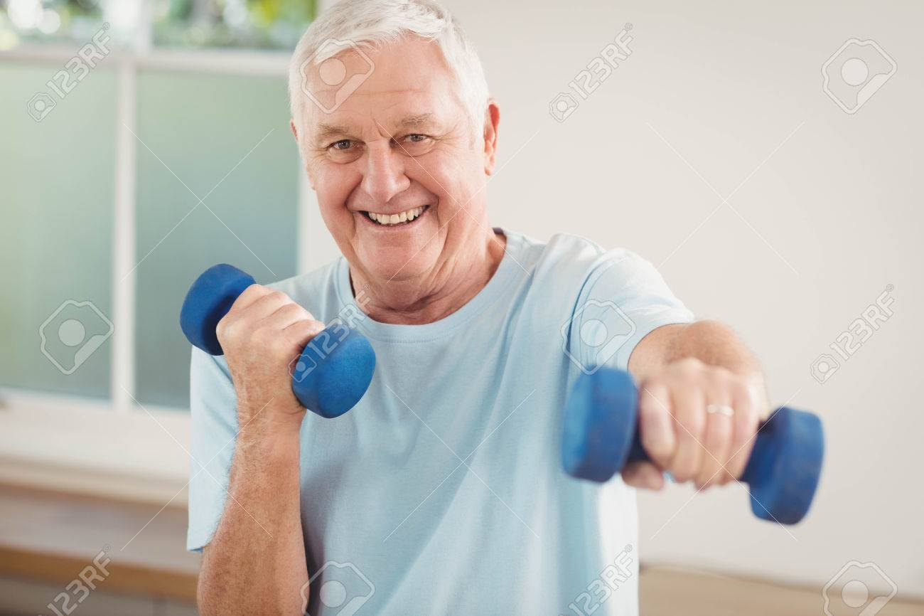 Portrait of senior man exercising with dumbbells at home Stock Photo - 52768559