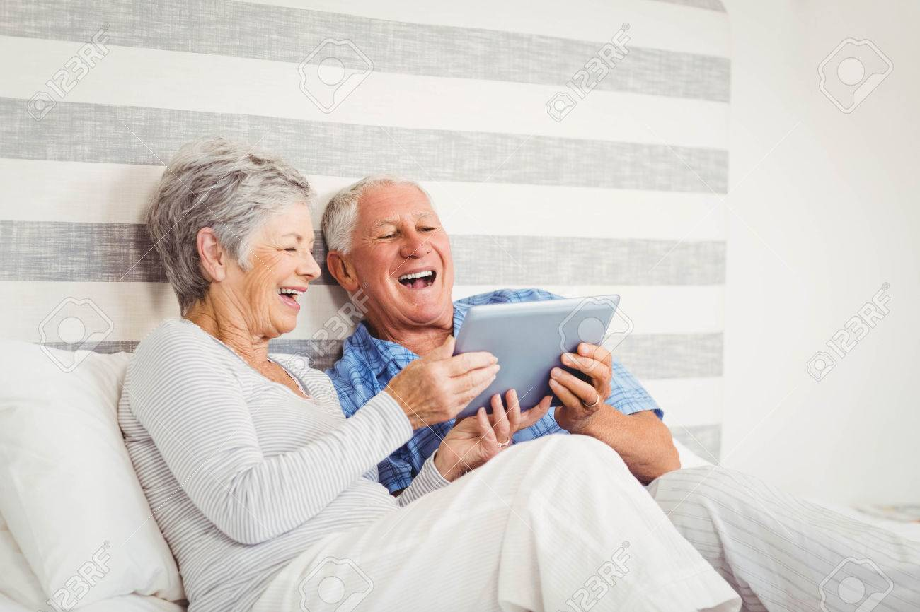 Senior couple laughing while using digital tablet in bedroom Stock Photo - 52776612