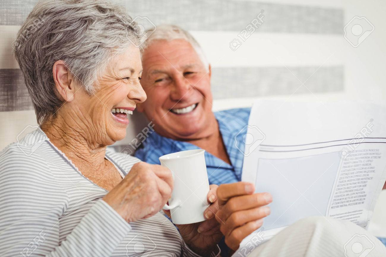 Senior couple laughing while reading newspaper in bedroom - 52777190