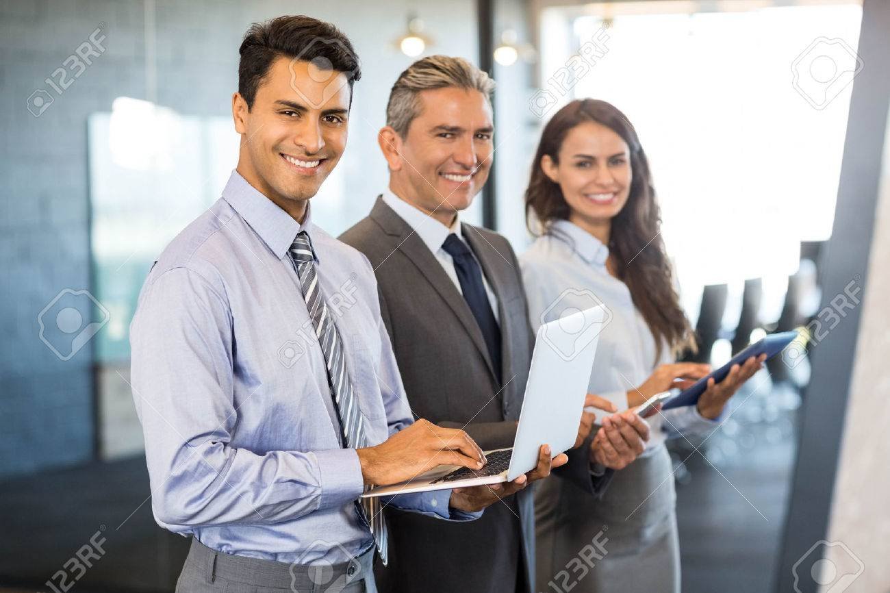 Businesspeople standing in a row and using mobile phone, lap top and digital tablet in office Stock Photo - 52782477