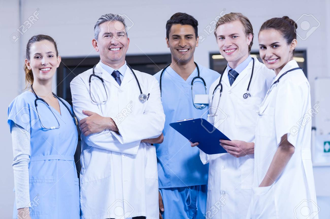Portrait of medical team standing together and smiling in hospital - 52845179