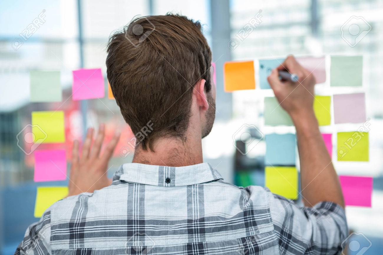 Hipster man writing on post-it in office Standard-Bild - 52799891